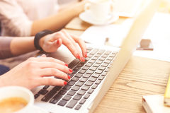 Jeunes femmes gaies travaillant sur des ordinateurs portables ensemble Photo stock