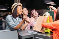 Jeunes femmes heureuses achetant des vêtements et regardant des paniers Image libre de droits