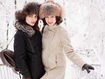 Jeunes femmes heureuses adorables de brune tenant des mains dans le chapeau de fourrure ayant la forêt neigeuse de parc d'hiver d Photographie stock