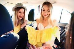 Jeunes femmes heureuses après avoir fait des emplettes ensemble dans la voiture Photos stock