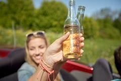 Jeunes femmes heureuses avec des boissons dans la voiture convertible Image libre de droits