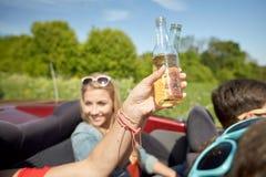 Jeunes femmes heureuses avec des boissons dans la voiture convertible Images stock