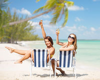 Jeunes femmes heureuses avec des boissons prenant un bain de soleil sur la plage Photos stock