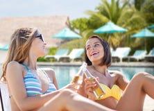 Jeunes femmes heureuses avec des boissons prenant un bain de soleil sur la plage Image libre de droits