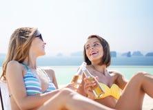 Jeunes femmes heureuses avec des boissons prenant un bain de soleil sur la plage Photographie stock