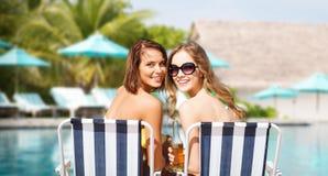 Jeunes femmes heureuses avec des boissons prenant un bain de soleil sur la plage Images stock