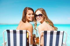 Jeunes femmes heureuses avec des boissons prenant un bain de soleil sur la plage Photographie stock libre de droits