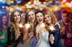 Jeunes femmes heureuses avec des cierges magiques à la boîte de nuit Image stock