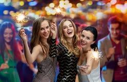Jeunes femmes heureuses avec des cierges magiques à la boîte de nuit Images libres de droits