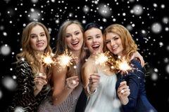 Jeunes femmes heureuses avec des cierges magiques au-dessus de neige Photos libres de droits