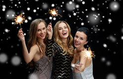 Jeunes femmes heureuses avec des cierges magiques au-dessus de neige Photographie stock