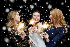 Jeunes femmes heureuses avec des cierges magiques au-dessus de neige Images libres de droits