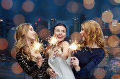Jeunes femmes heureuses avec des cierges magiques au-dessus de ville de nuit Photo libre de droits