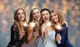 Jeunes femmes heureuses avec des cierges magiques au-dessus des lumières Image stock
