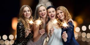Jeunes femmes heureuses avec des cierges magiques la nuit nouvelle année Images libres de droits