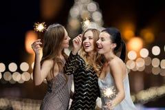 Jeunes femmes heureuses avec des cierges magiques la nuit nouvelle année Photo libre de droits