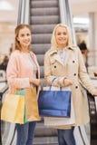 Jeunes femmes heureuses avec des paniers dans le mail Photographie stock