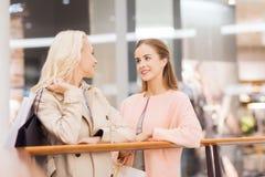 Jeunes femmes heureuses avec des paniers dans le mail Photographie stock libre de droits