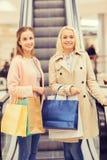 Jeunes femmes heureuses avec des paniers dans le mail Photos stock