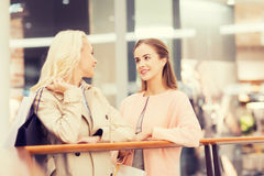 Jeunes femmes heureuses avec des paniers dans le mail Image stock