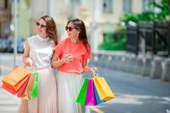 Jeunes femmes heureuses avec des paniers marchant le long de la rue de ville Vente, consommationisme et concept de personnes Photographie stock