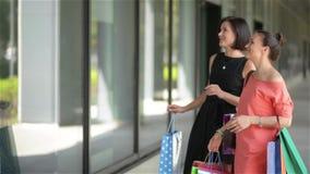 Jeunes femmes heureuses avec des sacs en papier d'achats dirigeant le doigt à la fenêtre de boutique dans la ville, la vente, le  banque de vidéos