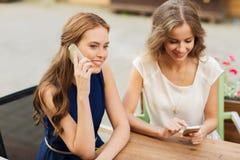 Jeunes femmes heureuses avec des smartphones au café extérieur Photographie stock