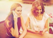 Jeunes femmes heureuses avec des smartphones au café extérieur Photos stock