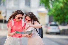 Jeunes femmes heureuses avec la carte touristique marchant sur la rue européenne Images stock