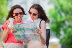 Jeunes femmes heureuses avec la carte touristique marchant sur la rue européenne Photos stock