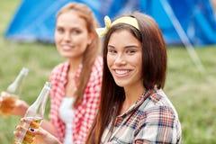Jeunes femmes heureuses avec la tente et boissons au terrain de camping Photographie stock libre de droits