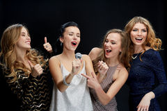 Jeunes femmes heureuses avec le karaoke de chant de microphone Photographie stock