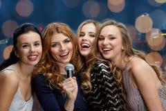 Jeunes femmes heureuses avec le karaoke de chant de microphone Photos libres de droits