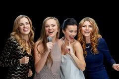 Jeunes femmes heureuses avec le karaoke de chant de microphone Photo stock