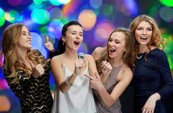 Jeunes femmes heureuses avec le karaoke de chant de microphone Images stock