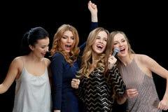 Jeunes femmes heureuses avec le karaoke de chant de microphone Photo libre de droits