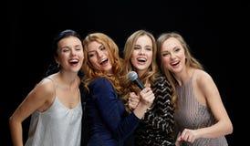 Jeunes femmes heureuses avec le karaoke de chant de microphone Photographie stock libre de droits