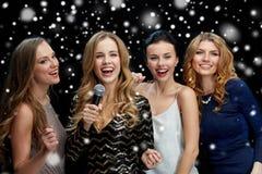 Jeunes femmes heureuses avec le karaoke de chant de microphone Photos stock