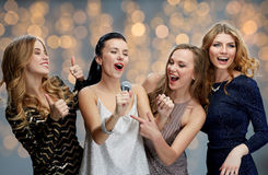 Jeunes femmes heureuses avec le karaoke de chant de microphone Image stock