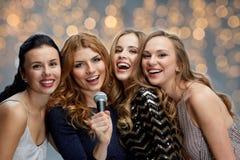 Jeunes femmes heureuses avec le karaoke de chant de microphone Images libres de droits