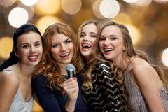 Jeunes femmes heureuses avec le karaoke de chant de microphone Image libre de droits