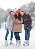 Jeunes femmes heureuses avec le smartphone sur la piste de patinage Image stock