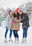 Jeunes femmes heureuses avec le smartphone sur la piste de patinage Photos libres de droits
