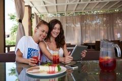 Jeunes femmes heureuses ayant la vidéoconférence sur le pavé tactile tout en se reposant en café moderne dans le jour d'été, Photographie stock libre de droits