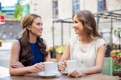 Jeunes femmes heureuses buvant du café au café extérieur Photos stock