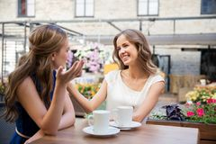 Jeunes femmes heureuses buvant du café au café extérieur Photo libre de droits