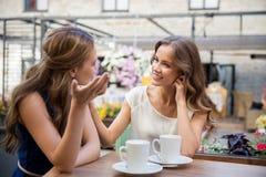 Jeunes femmes heureuses buvant du café au café extérieur Photographie stock