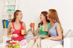 Jeunes femmes heureuses buvant du thé avec des bonbons à la maison Image stock