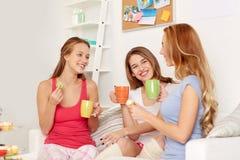 Jeunes femmes heureuses buvant du thé avec des bonbons à la maison Image libre de droits