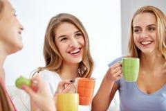 Jeunes femmes heureuses buvant du thé avec des bonbons à la maison Images stock